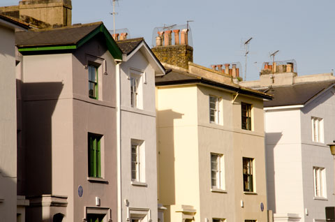 Houses painted in pale colours in the scenic Primrose Hill area of London, England