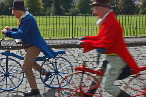 one man in blue coat and another in red coat riding velocipedes during Jane Austen Festival in Bath