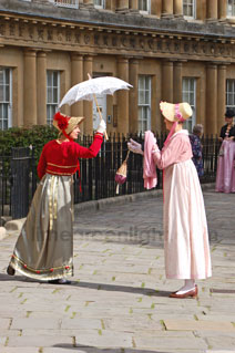 Woman in regency costume passing a parasol to another woman in costume