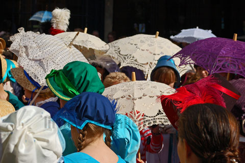colourful image of bonnets and parasols on the heads of promenaders during Bath Jane Austen Festival