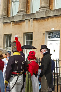 Two men and a woman in historic costume in Royal Crescent Bath