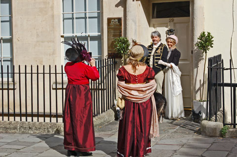 two women in red and a couple in dark blue and cream costumes in the Jane Austen Festival Bath