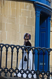 woman in regency costume passing a bright blue door in historic centre of Bath