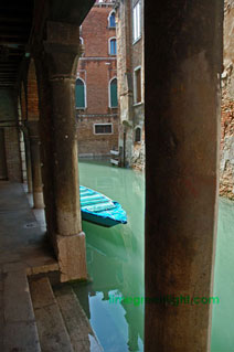 Venice canal and boat showing the green lagoon waters