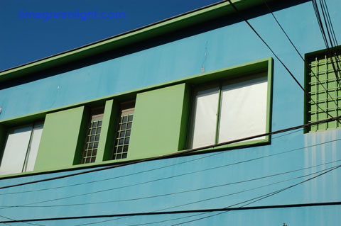 blue building with power lines in Valparaiso accentuating green hues and lines