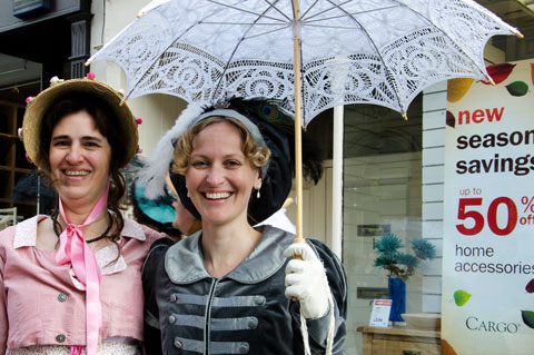 promenaders in costume contrasting with a street window display at the Jane Austen Festival in Bath 2011
