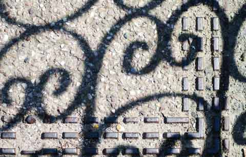 pavement art of shadows from fences