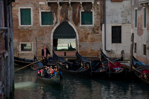 gondolas on a canal in front of a building with one containing tourists